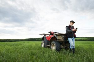 Farmer with Quad in field on cell phone